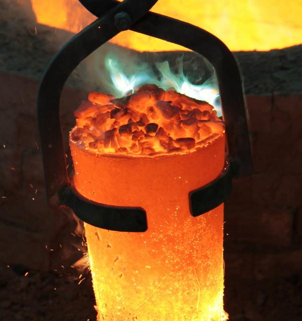 Bils eines Tiegels mit heißem Messing. Teile des Zinks verbrennen mit grelle Flamme.