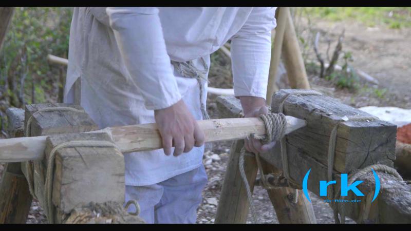 Der Lehmkern der Bienenkorbglocke wird auf einer Holzspindel aufgebaut. Im Unterschied zu späteren Jahrhunderten, werden karolingische Glocken horizontal liegend geformt.